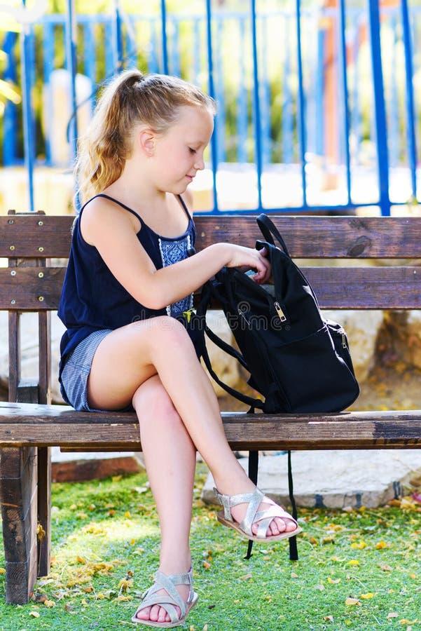 Fille d'adolescent préparant le sac à dos avec des fournitures scolaires image stock