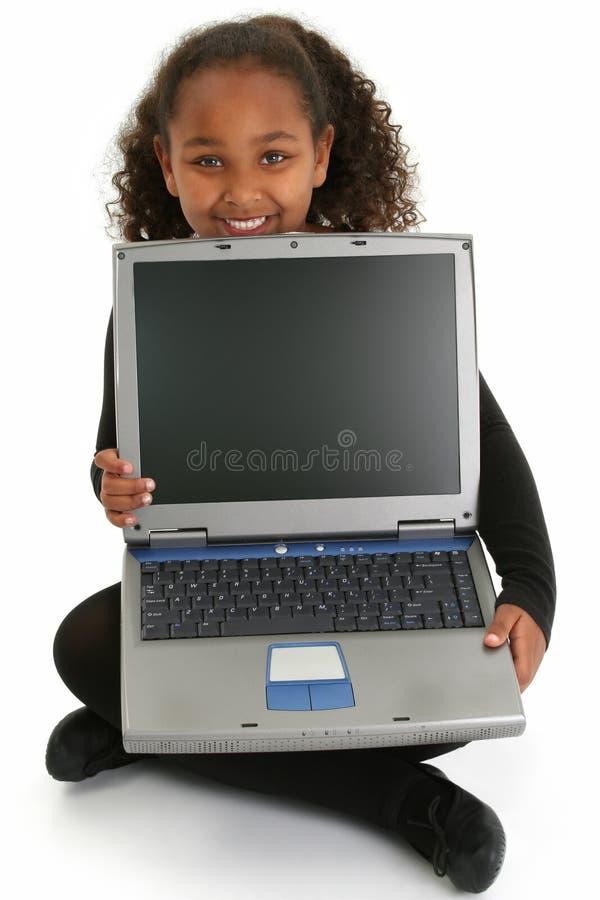 Fille d'Adorablel sur l'étage avec l'ordinateur portatif images stock