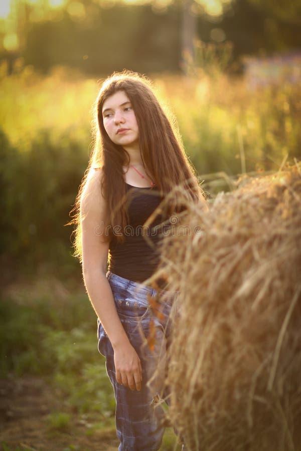 Fille d'agriculteur d'adolescent avec la fin de meule de foin vers le haut de la photo photo libre de droits