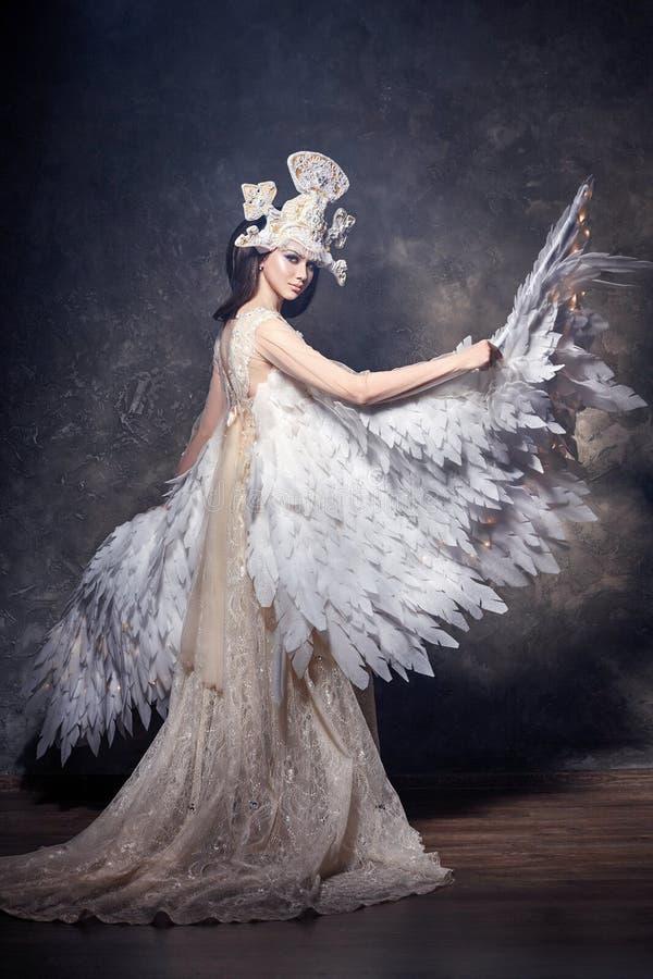 Fille d'ange d'art avec l'image de fée d'ailes Princesse de cygne, reine des anges Belle robe avec des ailes Verticale de beauté  images libres de droits