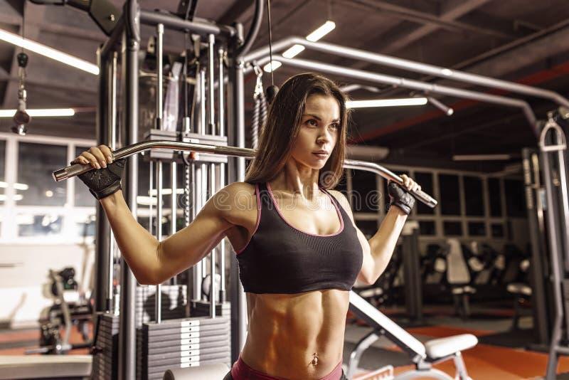 Fille d'athlète dans les vêtements de sport établissant et formant ses bras et épaules avec la machine d'exercice dans le gymnase images stock