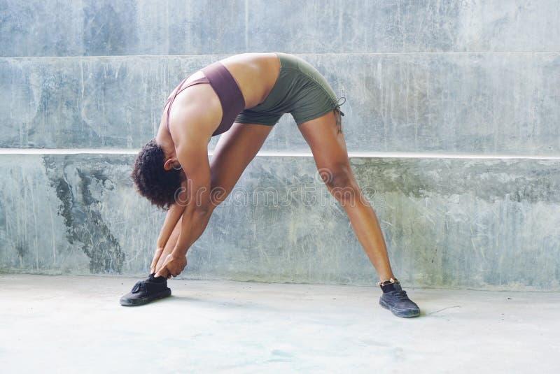 Fille d'athlète d'habitant des îles du Pacifique avec des routines de exercice de exécution Afro étirant le contact d'orteil images stock