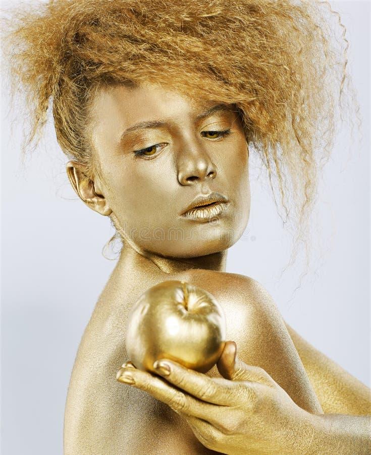 Fille d'or avec la pomme photo stock