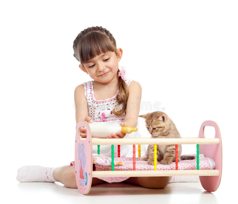 Fille d'enfant alimentant et jouant le chat de chaton photos stock
