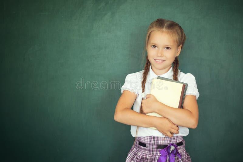 Fille d'enfant avec le livre Petite écolière dans des vêtements uniformes tenant le livre sur le fond vert de tableau noir De nou images libres de droits