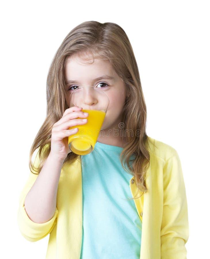 Fille d'enfant buvant du jus d'orange d'isolement sur le blanc photos libres de droits