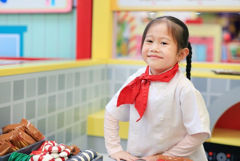 Fille d'enfant dans un costume du petit chef faire la pizza, faisant cuire le concept d'enfant images libres de droits