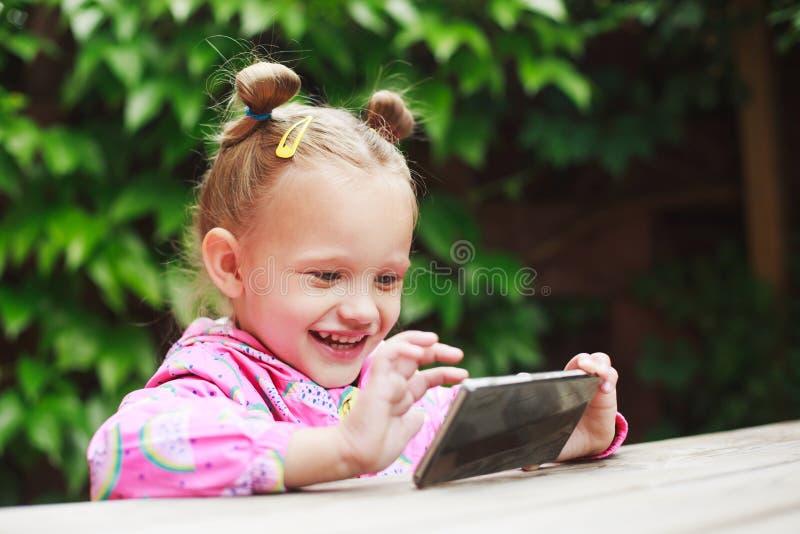 Fille d'enfant en bas âge à l'aide d'un téléphone intelligent images libres de droits