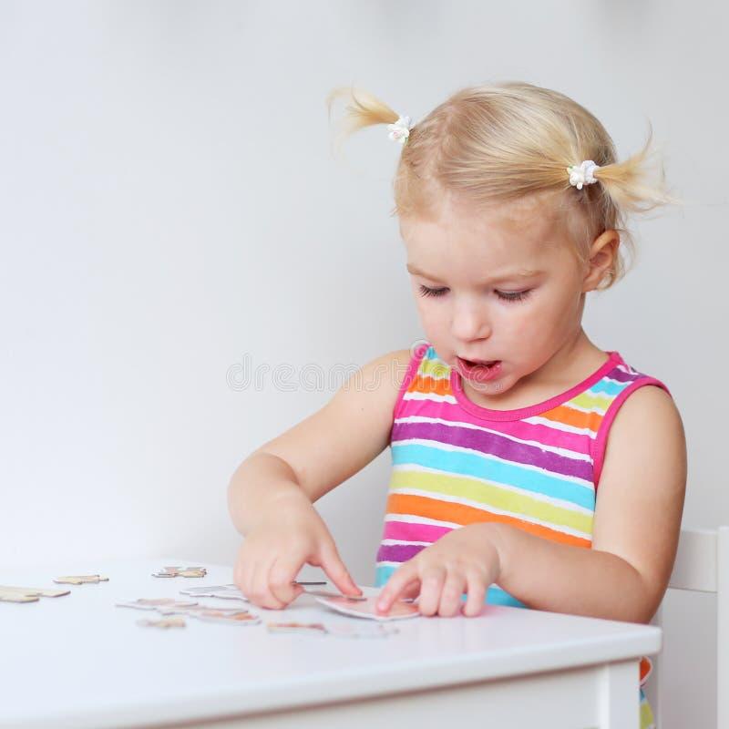 Fille d'enfant en bas âge assemblant le puzzle denteux à l'intérieur images stock