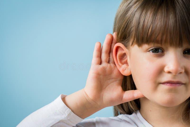 Fille d'enfant en bas ?ge avec le probl?me d'audition sur le fond bleu-clair Fermez-vous, copiez l'espace images libres de droits