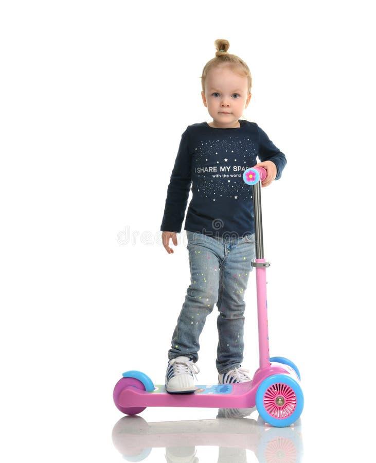 Fille d'enfant en bas âge de petit enfant apprenant à monter et équilibrer sur la poussée t image stock