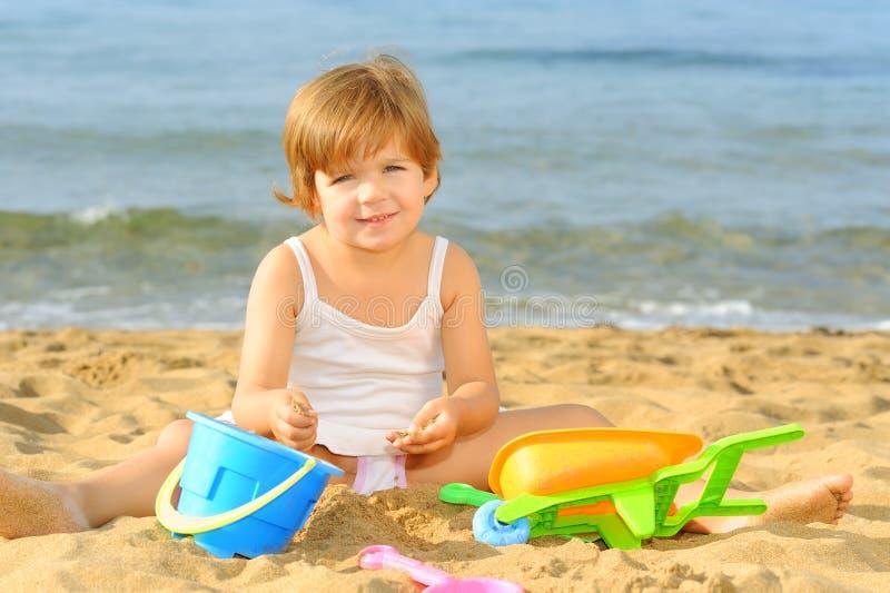Fille d'enfant en bas âge jouant avec ses jouets à la plage images stock