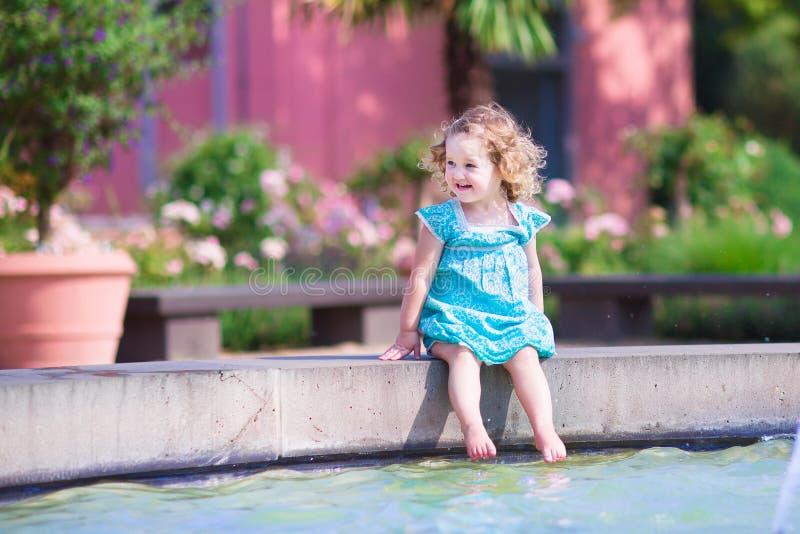 Fille d'enfant en bas âge jouant dans une fontaine photographie stock