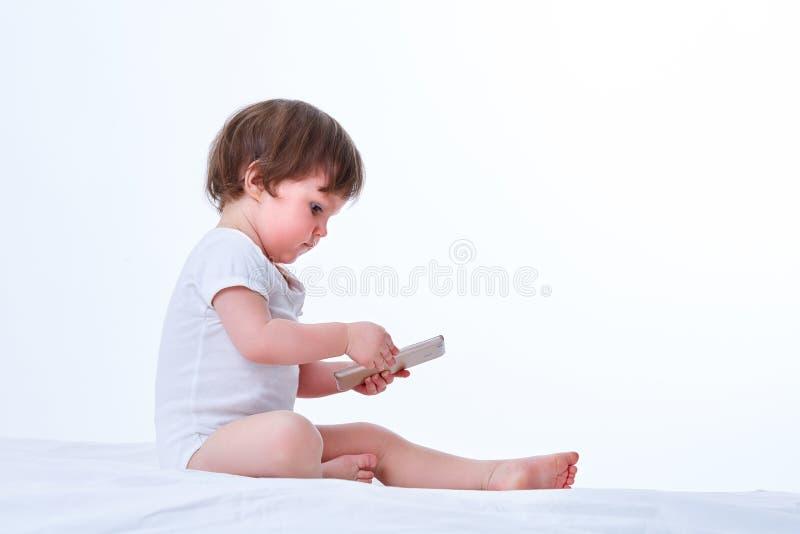 Fille d'enfant en bas âge s'asseyant et jouant avec le téléphone portable mobile d'isolement sur un fond blanc photographie stock