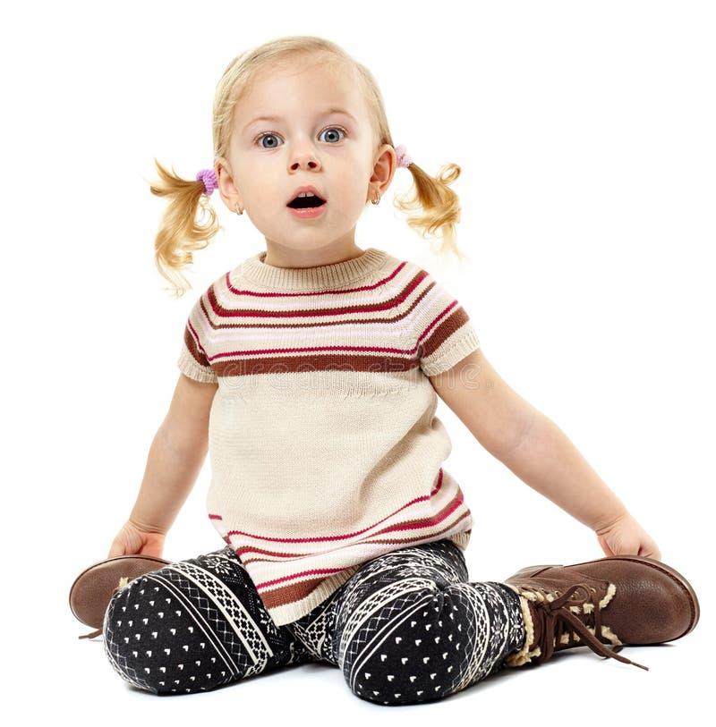 Fille d'enfant en bas âge s'asseyant sur le plancher et exprimant la surprise photo libre de droits