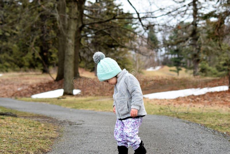 Fille d'enfant en bas âge sur le chemin sylvatique regardant vers le bas photos libres de droits