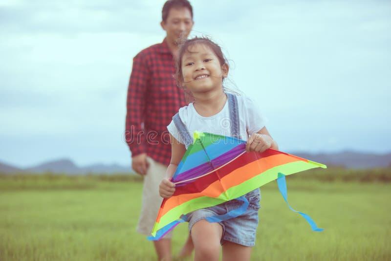 Fille d'enfant et père asiatique avec un fonctionnement de cerf-volant et heureux sur le montant éligible maximum photos libres de droits
