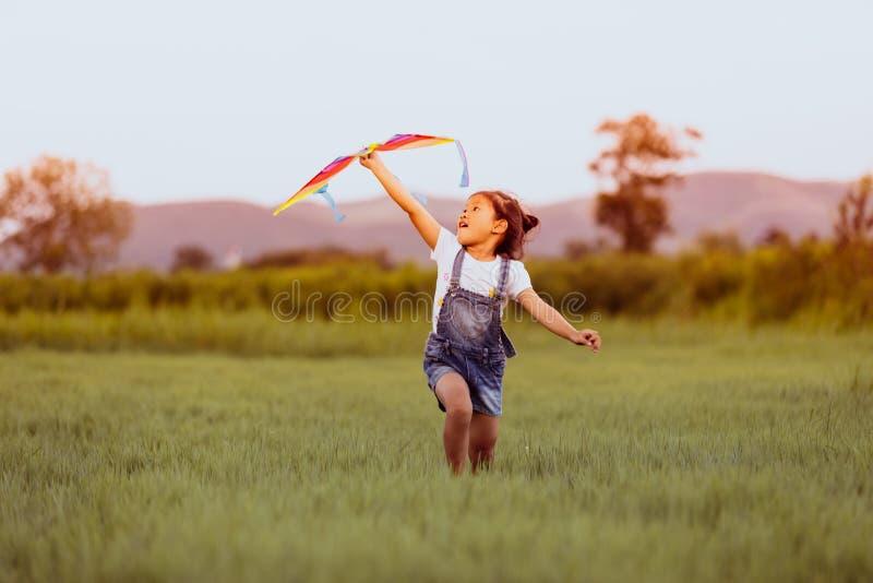 Fille d'enfant et père asiatique avec un fonctionnement de cerf-volant et heureux sur le montant éligible maximum images libres de droits
