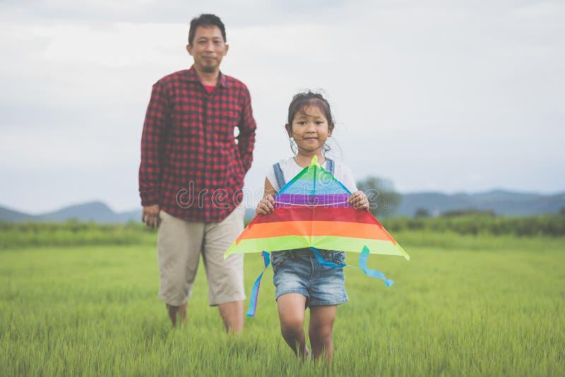 Fille d'enfant et père asiatique avec un fonctionnement de cerf-volant et heureux sur le montant éligible maximum photo stock
