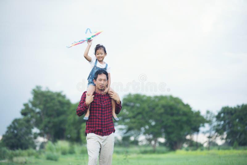 Fille d'enfant et père asiatique avec un fonctionnement de cerf-volant et heureux sur le pré en été en nature photos stock