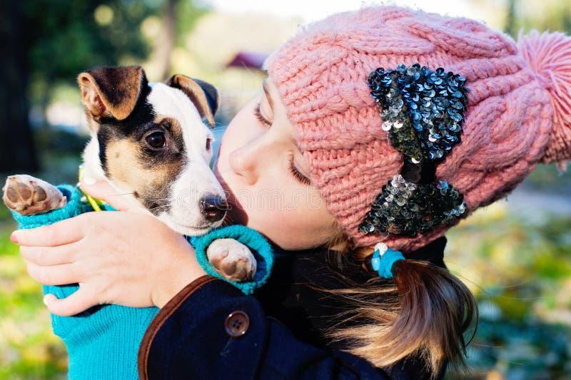 Fille d'enfants embrassant son chienchien de terrier de chiot sur le parc image stock