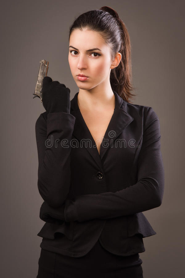 Fille d'espion dans un noir avec l'arme à feu photographie stock