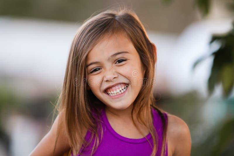 Fille d'une chevelure brune de sourire enthousiaste de quatre ans images stock