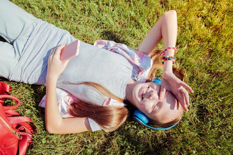 Fille d'une chevelure rouge avec plaisir de positif se trouvant sur l'herbe verte photographie stock
