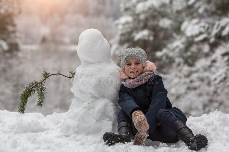 Fille d'ute de ¡ de Ð la petite s'assied dans la neige avec le bonhomme de neige gibier photographie stock