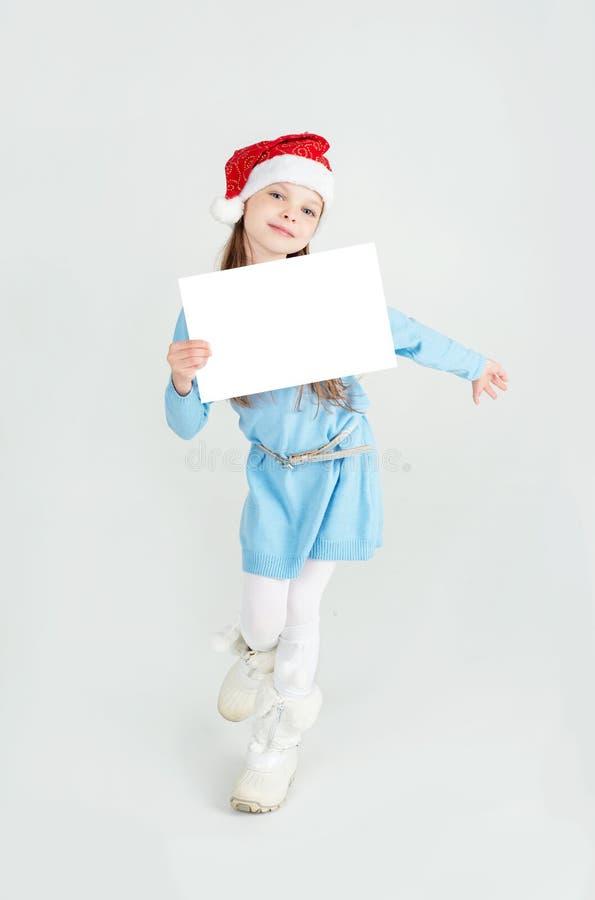 Download Fille D'ute De ¡ De Ð Dans Le Chapeau De Santa Claus Avec Une Feuille Blanche De Papier Blanc ¡ De Ð Image stock - Image du fille, chapeau: 45357365