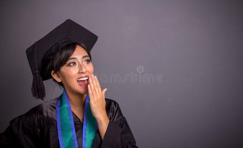 Fille dans des équipements d'obtention du diplôme voyant une chose d'une manière amusante choquante photo stock