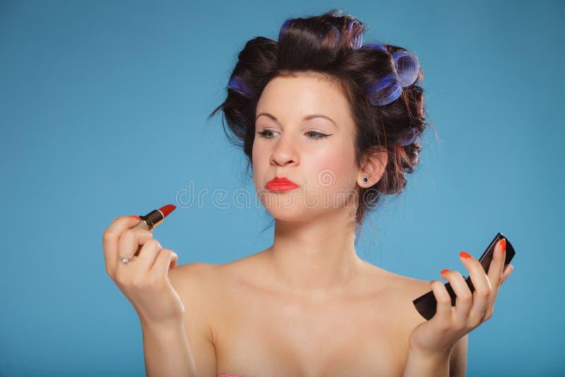 Fille dans des bigoudis de cheveux appliquant le rouge à lèvres rouge photos libres de droits