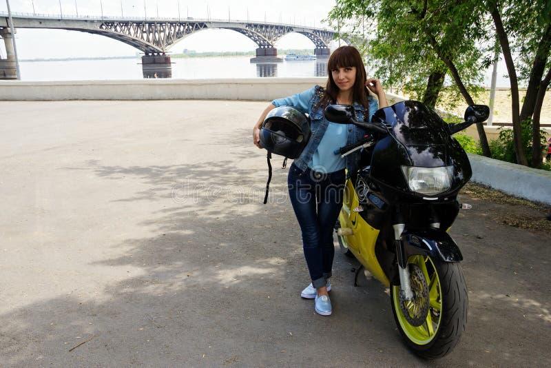 Fille dans des jeans avec une moto images stock