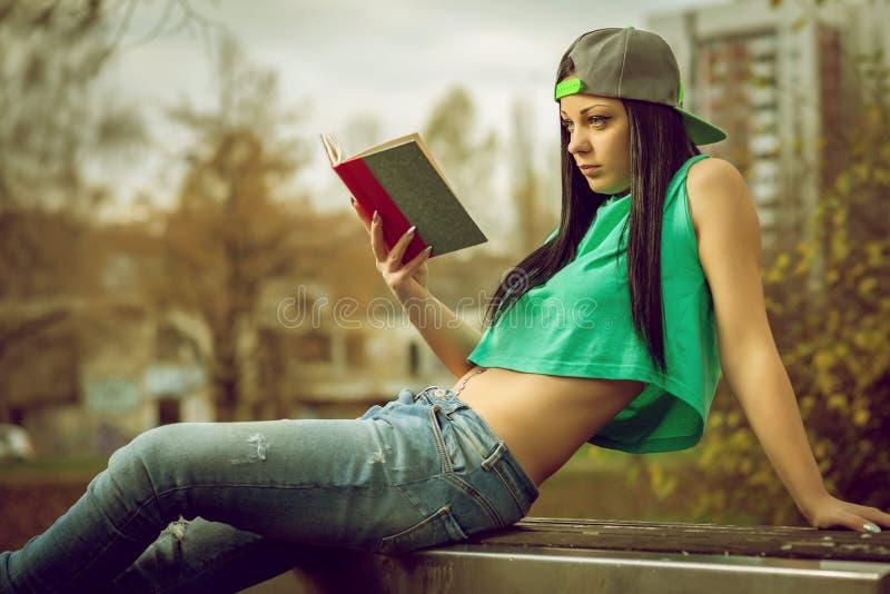 Fille dans des jeans lisant un livre sur le banc photos stock