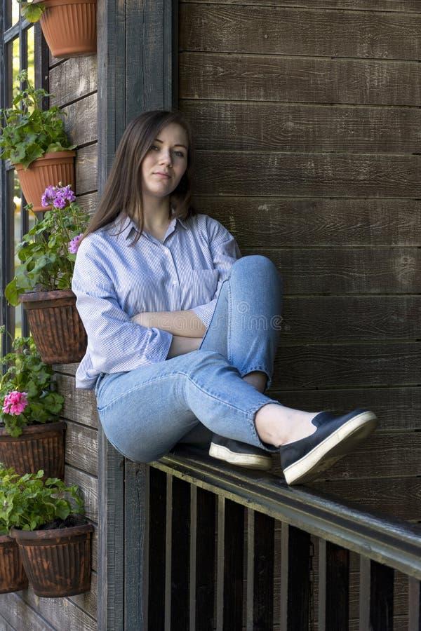 Fille dans des jeans se reposant sur le porche photo libre de droits