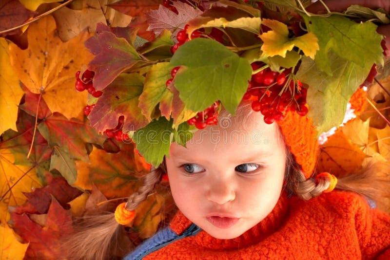 Fille dans des lames oranges d'automne. Extérieur. images stock
