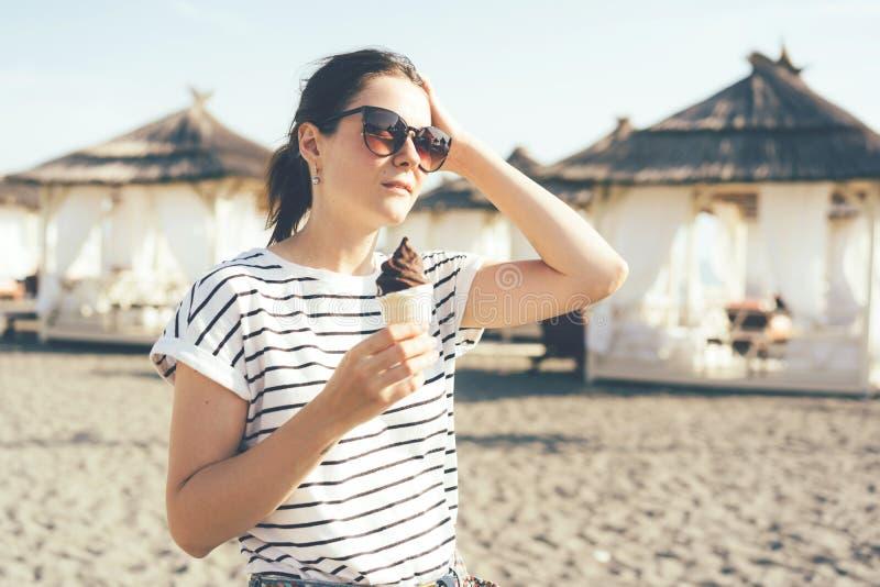 Fille dans des lunettes de soleil avec la crème glacée  photographie stock