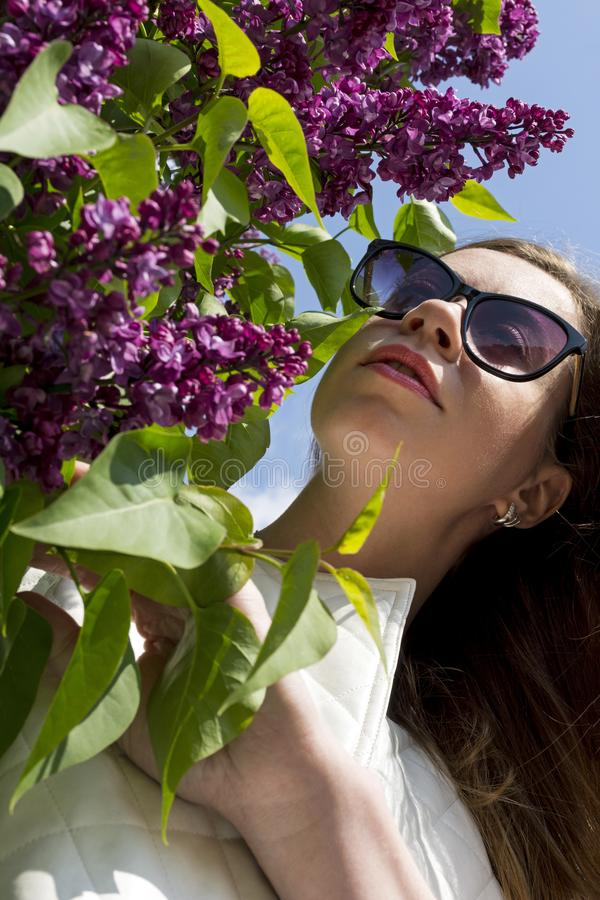 Fille dans des lunettes de soleil près de Bush lilas de floraison, le visage n du ` s de fille photographie stock