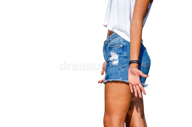 Fille dans des shorts de denim sur un fond blanc photos stock