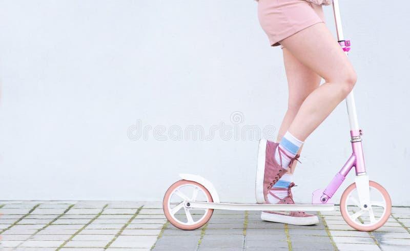 Fille dans des tours roses de vêtements sur un scooter rose sur le fond d'un mur blanc photo stock