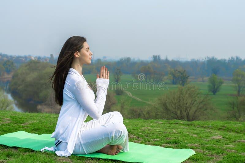 Fille dans des vêtements blancs faisant des exercices de yoga images libres de droits