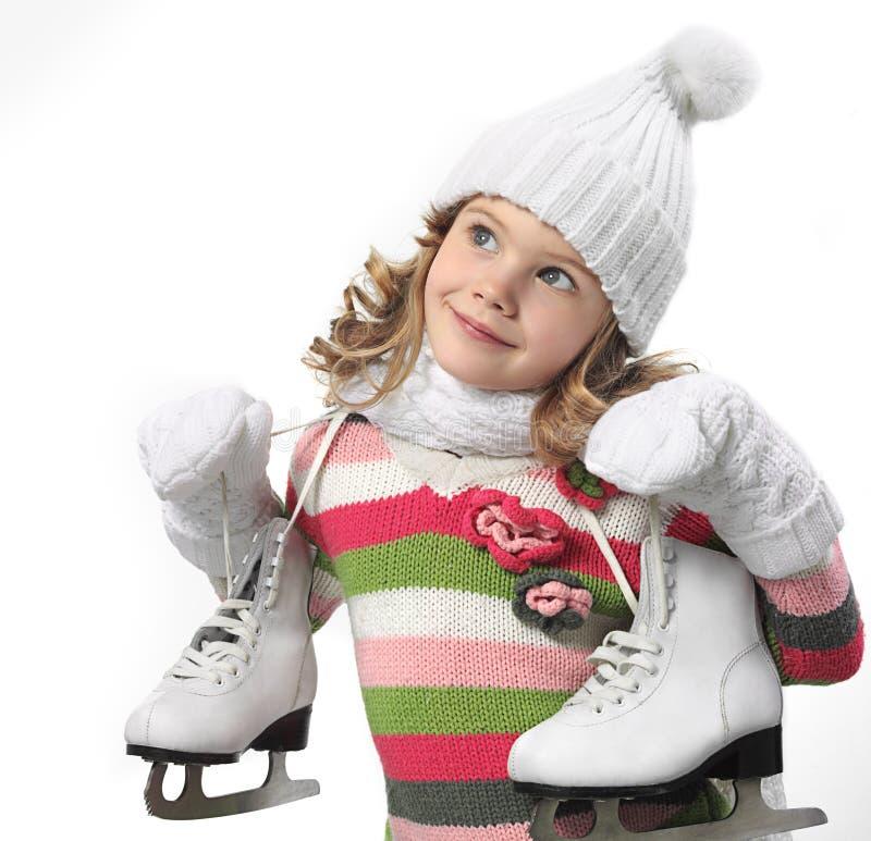 Fille dans des vêtements d'hiver avec le chiffre patins photographie stock