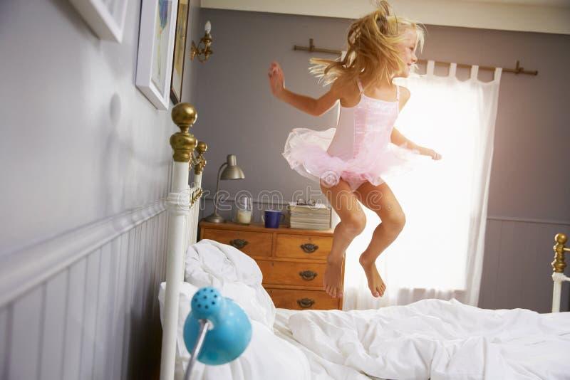 Fille dans l'équipement de ballerine sautant sur le lit de parents images stock