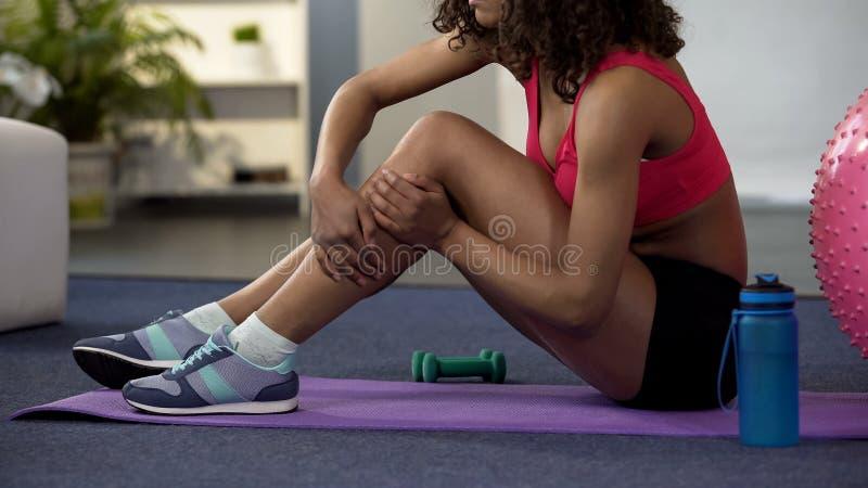Fille dans l'équipement de gymnase se reposant sur le plancher et massant la jambe à l'etroit, muscle tendu image stock