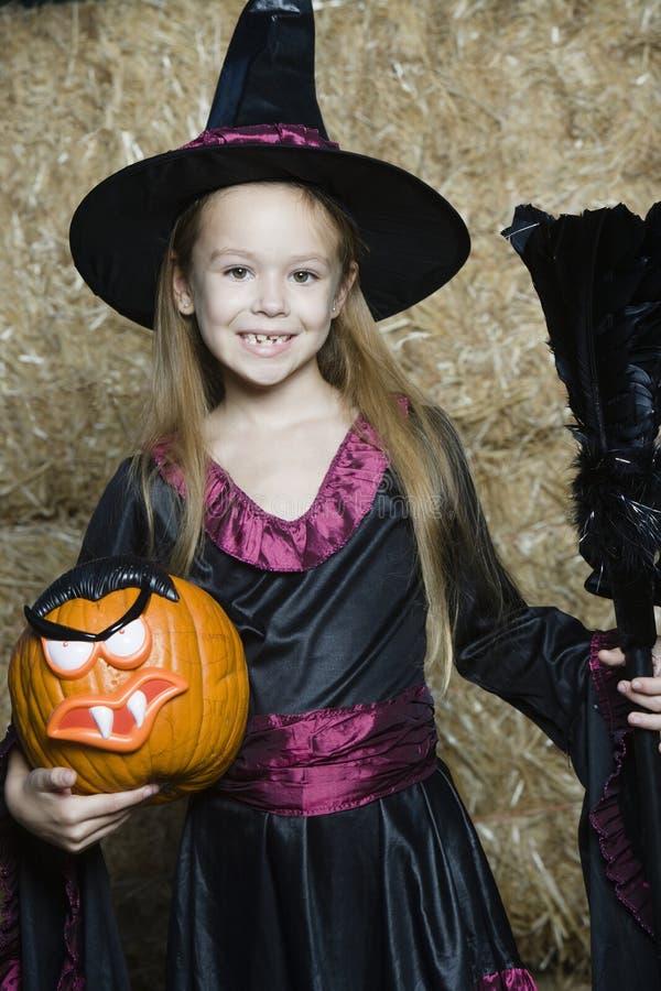 Fille dans l'équipement de Halloween tenant la Jack-O-lanterne et le manche à balai images libres de droits