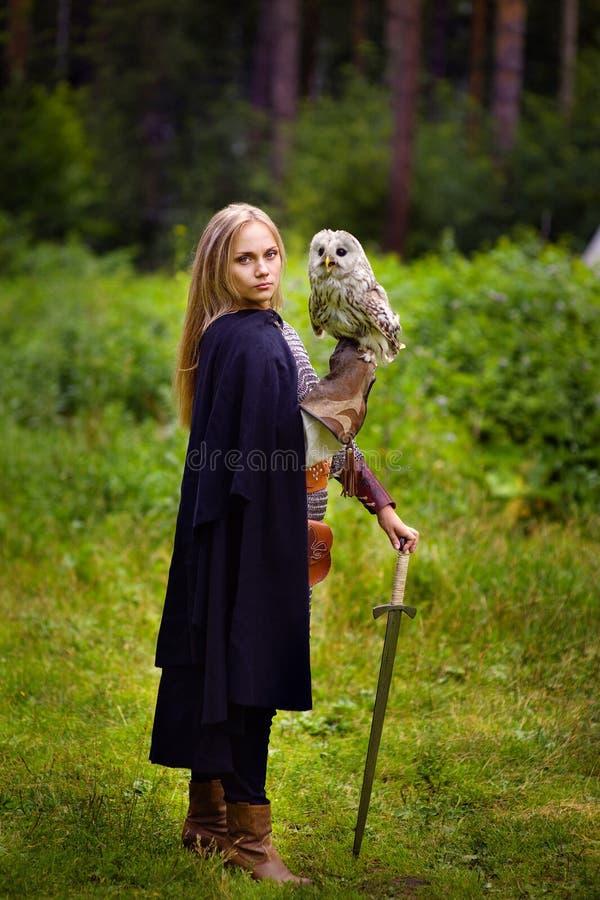 Fille dans l'armure et avec une épée tenant un hibou image libre de droits