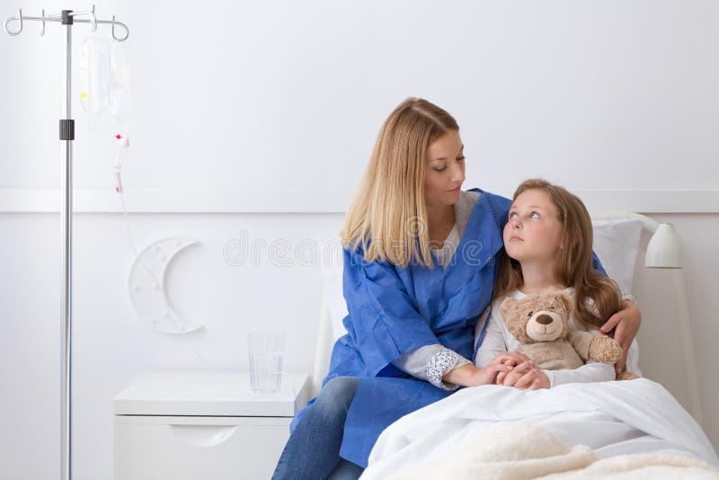Fille dans l'hôpital et mère tenant sa main images stock