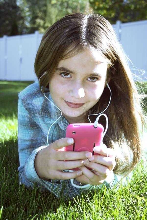 Fille dans l'herbe écoutant la musique image libre de droits