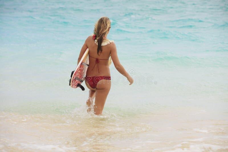 Fille dans l'océan avec sa planche de surfing image stock