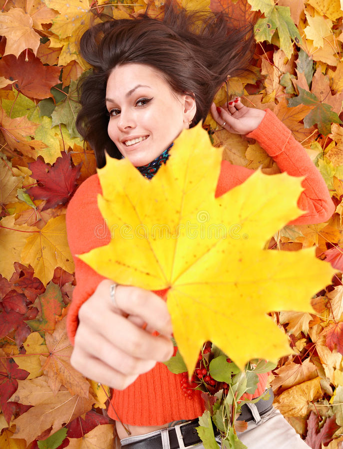 Fille dans l'orange sur le feuillage d'automne avec la lame jaune. photos libres de droits